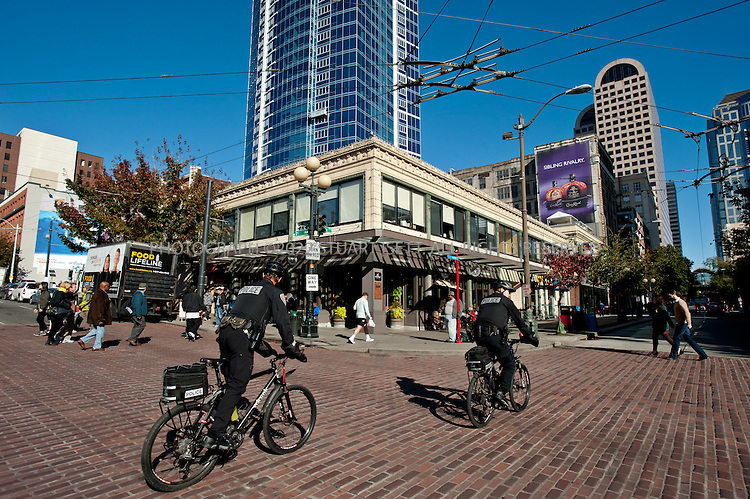 10/27/2010--Seattle, WA, USA..Bicycle police in downtown Seattle...Seattle consistently has been rated one of the top spots in the USA for bicycling. A substantial proportion of Seattleites use their bicycles for recreation or transportation. It is estimated that about 36% of Seattle's 520,000 citizens engage in recreational bicycling, and between 4,000 and 8,000 people bicycle commute in Seattle each day, depending on the time of year and weather conditions. The city's 'Bicycle Program' has been working steadily toward developing an urban trail system to accommodate bicyclists. Urban trails include shared use paths, bike lanes, signed bike routes, arterials with wide shoulders, and pedestrian pathways. Seattle has about 28 miles of shared use paths, 22 miles of on-street, striped bike lanes, and about 90 miles of signed bike routes and is investing in more every year...Photograph by Stuart Isett