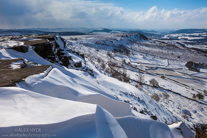 Curbar Edge looking towards Baslow Edge, with huge snow drifts in the foreground during the heavy snowfall of March 2013. Peak District National Park, Derbyshire, UK.