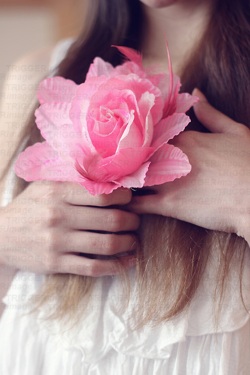 faceless portrait of a girl holding a pink rose over her chest