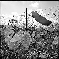 A bullet hole marks a target trapped against the barbed wire of an Israeli military camp near a settlement on the edge of the occupied West Bank near Jerusalem, 1996.  Settlements are Jewish residential nodes in areas of Palestine/Jordan/Syria/Egypt occupied after the wars against Jordan, Egypt and Syria. Part of SCARS series. Photo Greg Marinovich / South