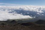 Mauna Kea, Big Island of Hawaii, Hawaii; looking down at cinder cones from above the clouds while driving down from the summit of the Mauna Kea Observatories (MKO), currently there are 13 independent multi-national astronomical research facilities located on the summit. Mauna Kea's altitude and isolation in the middle of the Pacific ocean make it an ideal location for astronomical observation.