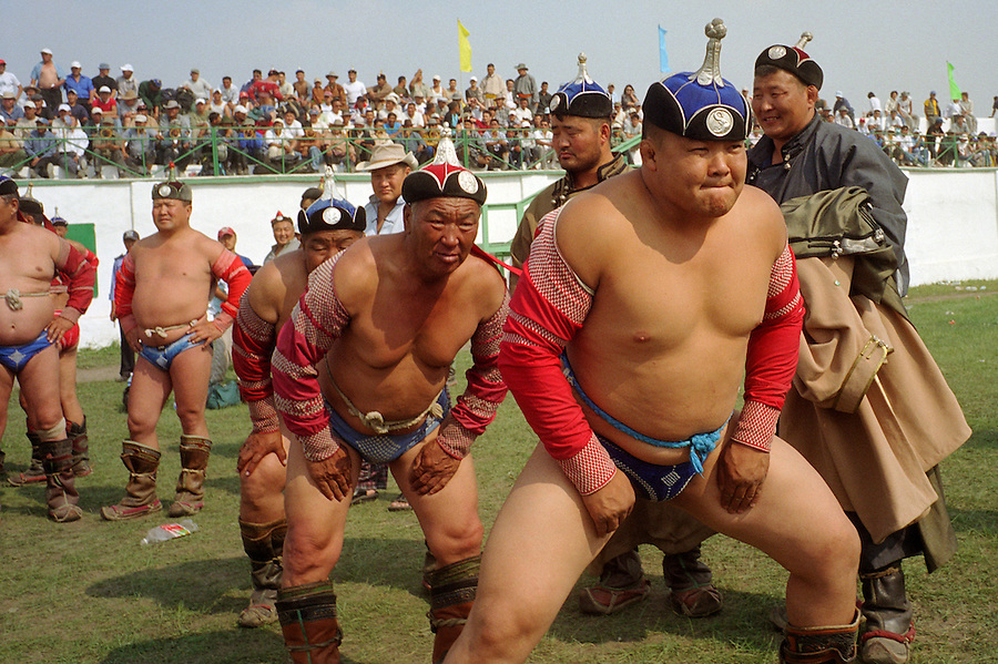 Zuunmod, Mongolia, July 2003..Competitors and spectators at the Mongolian Wrestling contests in the Llama Naadam. Wrestlers limber up before a bout.