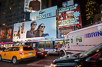 Advertising on billboards for Lacoste competes with Larry Flynt's Hustler Club and other advertisements in Times Square in New York on Tuesday, November 25, 2014. (© Richard B. Levine)
