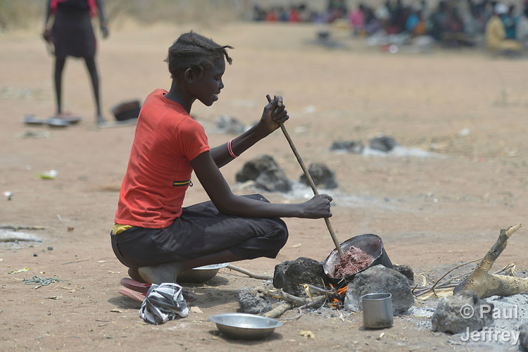 A girl cooks beans that her family received from the ACT Alliance on April 7, 2017, in Rumading, a village in South Sudan's Lol State where more than 5,000 people, displaced from their homes by drought and conflict, remain in limbo. In early 2017, they set out walking for Sudan, seeking better conditions, but were stopped from crossing the border. They remained camped out under the trees at Rumading, eating wild leaves as the rainy season approached.<br /> <br /> In early April, Norwegian Church Aid, a member of the ACT Alliance, began drilling a well in the informal settlement and distributed sorghum, beans and cooking oil to the most vulnerable families. The ACT Alliance is carrying out the emergency assistance in coordination with government officials and the local Catholic parish.