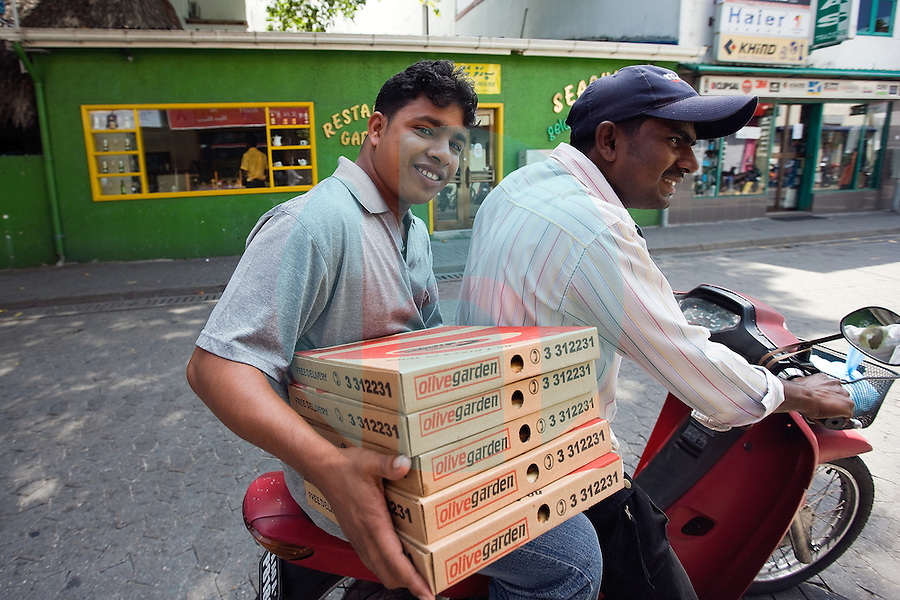 20081207_MALE, MALDIVES_ Men on a motorbike carry a load of pizzas in the Maldives capital island of Male, on Sunday, December 7th, 2008. Tourism is the main industry in the Maldives, contributing almost 20 percent to the GDP. Fisheries and trade follow close behind.  Photographer: Daniel J. Groshong/Tayo Photo Group