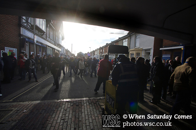 "Portsmouth 1 Southampton 1, 18/12/2012. Fratton Park, Championship. Portsmouth fans making their way into the main entrance to Fratton Park stadium before their club take on local rivals Southampton in a Championship fixture. Around 3000 away fans were taken directly to the game in a fleet of buses in a police operation known as the ""coach bubble"" to avoid the possibility of disorder between rival fans. The match ended in a one-all draw watched by a near capacity crowd of 19,879. Photo by Colin McPherson."