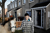 """Dublin, Ireland, January 5, 2011:.Luke, 12,  with his horse by their home on Bell Camp housing estate..Since the beginning of crisis, between 10 and 20 thousand horses have become homeless or went in the hands of the youths in urban areas. Lots of Irish people who used to buy horses for fun during the boom years of """"Celtic Tiger"""", now are abandoning them faced with expenditure of 35 Euro a week to properly maintain a horse. This animal previously worth 2000 Euro now can be purchased for as little as 80 Euro. New owners keep their horses in city greens, city ruins, or their house gardens, in very bad conditions. Most do not get much food, many are starving, dying, being mistreated..(Photo by Piotr Malecki / Napo Images)..Dublin, Irlandia, 5/01/2011:.Luke, 12 lat i jego kon przed domem na osiedlu mieszkaniowym Bell Camp..Od poczatku kryzysu od 10 do 20 tysiecy koni zostalo wyrzuconych na ulice przez wlascicieli nie chcacych placic okolo 35 Euro/tydzien za ich utrzymanie. Wpadaja one czesto w rece mlodziezy z ubogich dzielnic miasta, ktora handluje nimi, bije, glodzi, trzyma w skrajnie trudnych warunkach, w przydomowych ogrodkach lub ruinach budynkow i szaleje na nich po miescie. Kon, ktory byl wart 2000 Euro teraz moze byc kupiony za 80. .Fot: Piotr Malecki / Napo Images."""
