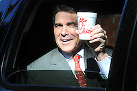 "CHARLESTON, South Carolina, January 14, 2012: Texas Governor Rick Perry rolled down his window and hoisted a Chick-Fil-A cup to a throng of media outside the ""Huckabee Forum 2: South Carolina Undecided,"" at the College of Charleston in Charleston, South Carolina."