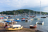 Boats in the harbour and family group on beach at coastal resort of Teignmouth in South Devon, England, UK
