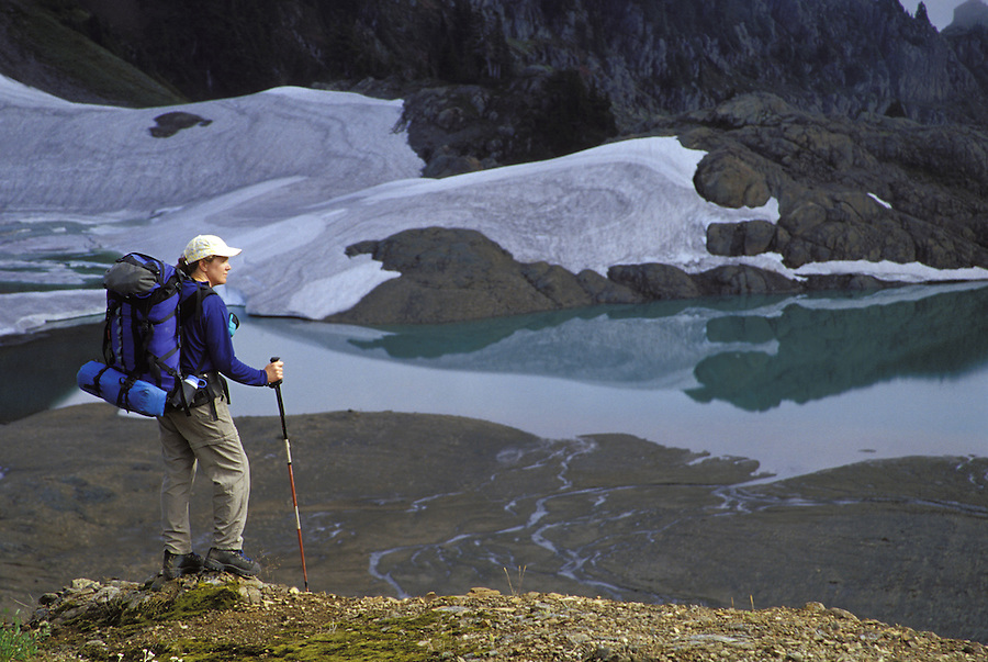 Hiker overlooking alpine lake and meadows, North Cascades, Cascade Mountains, Washington