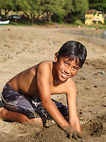 Boy playing in sand at Hanaka'o'o Beach (or Canoe Beach) on Maui.