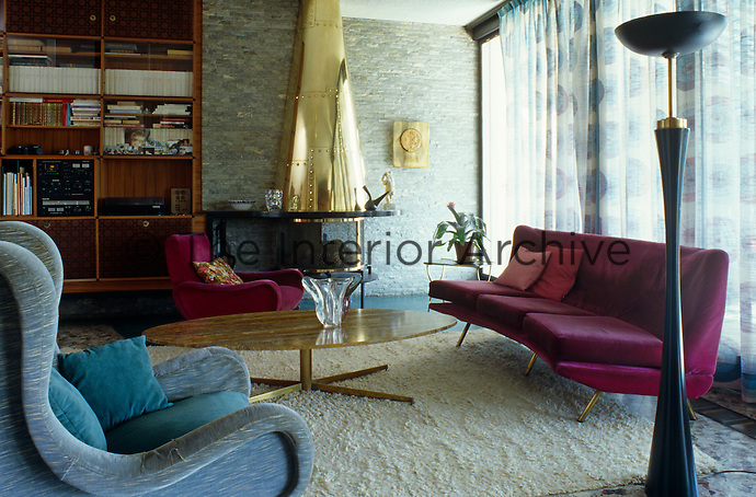 This 50s style living room is complete with retro furniture and bookcase and a conical brass fireplace