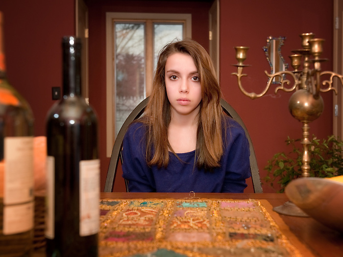 A teenage girl sitting at a dinning room table with wine