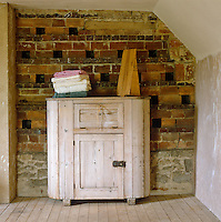 A bleached wood cupboard stands against a brick wall