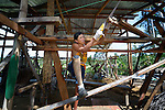 Rogelio Francisco builds a new house for his family in Concepcion, Philippines. The town bore the brunt of Typhoon Haiyan, known locally as Yolanda, in November 2013, and Francisco's house was flattened. Francisco has one prosthetic leg.