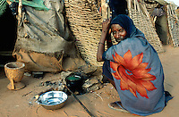 Sudan. West Darfur. Ryiadh. Ryiadh is located on the outskirts of the town of Al Geneina and is a camp for internally displaced people (IDP)) from the civil war. An elderly woman, wearing a fashionable veil with a red flower on her head, cooks in front of her poor living wood hut.© 2004 Didier Ruef