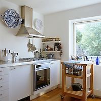One side of the open galley-style kitchen which is furnished with white units and stainless steel equipment