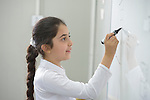 A student writes on the whiteboard in a class at the Al Bishara School, which is run by the Dominican Sisters of St. Catherine of Siena in Ankawa, near Erbil, Iraq. The students and the Dominican Sisters themselves were displaced by ISIS in 2014. The nuns have established schools and other ministries among the displaced.