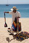 Beach vendor trying to make a sale to tourists, Cabo San Lucas, Baja California, Mexico