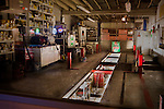 Photograph of an Oil Change/Mechanics Shop at night located in Downtown Sandpoint ID. The reflection of the neon beer signs from the bar across the street appears in the glass of the garage door in the left part of the frame.