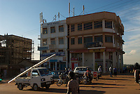 A suburb of Kampala, built on 'seven hills' -  everwhere buildings on hilltops bristle with mobile masts to provide line-of-sight coverage. The building boom is fuelled by a growth rate of X% over the last decade.