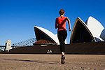 A jogger runs towards the Sydney Opera House.  Sydney, New South Wales, AUSTRALIA.