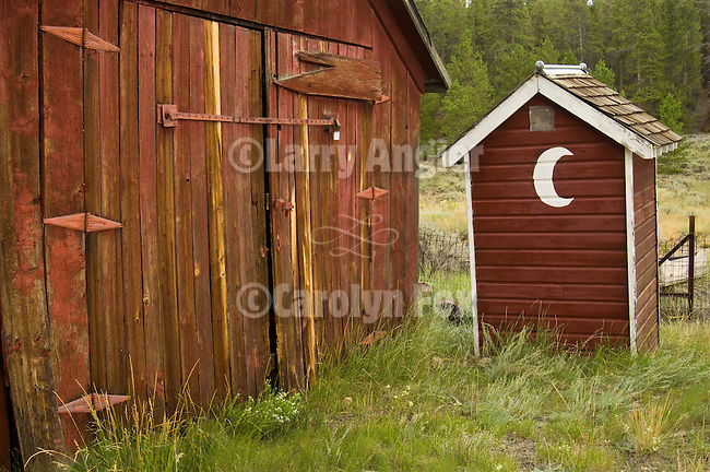 Red wooden outhouse with painted crescent moon behind the Dist. 11 Schoolhouse, Leadville, Colorado.