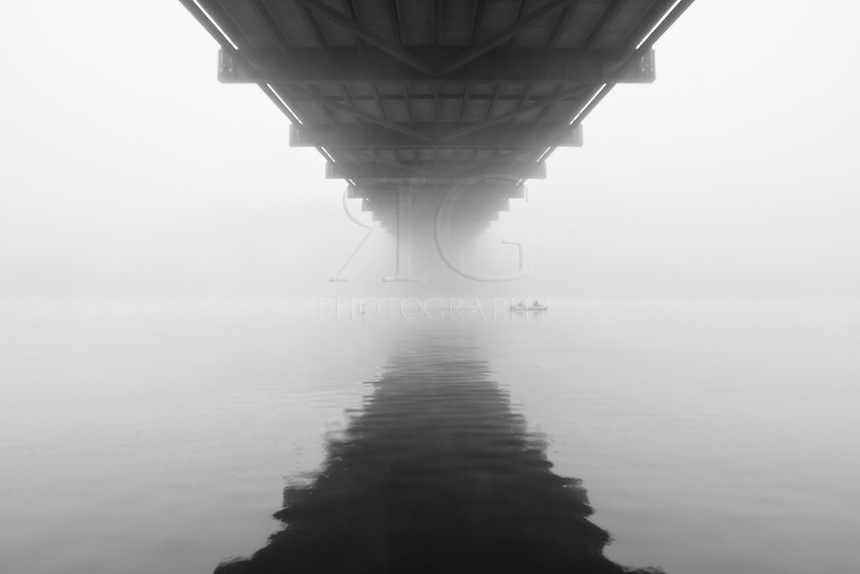 On a foggy morning, two fishermen drift beneath the 360 Bridge near Austin, Texas in this black and white photograph.