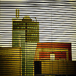 City buildings behind window blinds