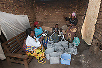 Africa, DRC, Democratic Republic of the Congo, S. Kivu, Katana. Women for Women project. Women from the Bulama group,  weaving baskets to sell in the local market, they take about 2 hours to make each one. Solange Bahadi (22yrs w/daughter), Georgetter Bysane (28, w/baby on back), Georgette Kavujwa (40, red hat),  Esperance Maneno (40 yrs, married 4 kids).