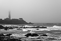 Fog nearly hides the top of the Pigeon Point Lighthouse but not the waves flowing over the rocky coast below.