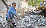A man salvages bent rebar from the rubble of a bombed building in the Al-Shalti refugee camp in Gaza. Residents of the Palestinian territory are still reeling from the death and destruction of the 2014 war with Israel, and the continuing siege of the seaside territory by the Israeli military.