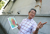 Motoharu Nakagawa, aged 69, saw the American B29 Bomber 'Bock's Car', carrying an atomic bomb destined for Kokura, but dropped over Nagasaki instead on August 9th 1945. He holds a map of Kokura showing the projected damage if the bomb had been dropped on the city, standign beside the wall of the armaments factory which was the intended target of the bombing..Kokura, Japan, 7th August 2005.