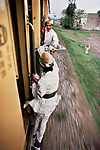 Breakfast Tea being passed between cars on the railway between Peshawar and Lahore,  Pakistan, 1983. <br />