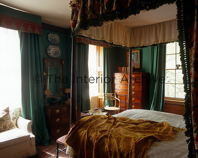 The bedroom is dominated by a four-poster bed and painted a rich dark green
