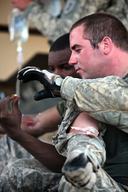 Spc. Bryan Hetherington, 22, of Appleton, Wis. and Spc. William Burgess, 23, of Tallahassee, Fla., two soldiers with Company A, 2nd Battalion, 2nd Infantry Regiment share a cigarette while receiving IVs for dehydration after a gun battle with Taliban fighters near the village of Zangabad in Panjwayi district, Kandahar province, Afghanistan. April 27, 2009. DREW BROWN/STARS AND STRIPES