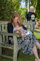 A mother  breastfeeding her child during a family outing to a local park and gardens, with a passer-by in the background.<br /> <br /> 11-06-2015<br /> Hampshire, England, UK<br /> <br /> &copy; Paul Carter / wdiip.co.uk