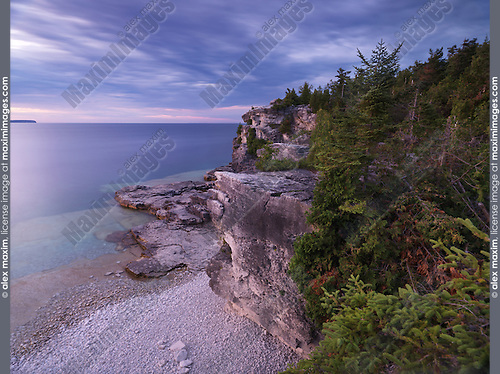 Beautiful sunset scenery of Georgian Bay rocky shore and cliffs covered with cedar trees. Bruce Peninsula National Park, Ontario, Canada.