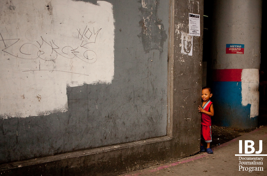 A child hides behind a wall near Recto station in Manila.