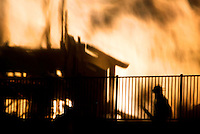 A San Diego firefighter watches a building burn out of control in the northeastern part of San Diego after is was one of four buildings set on fire in the region on September 19, 2003. Officials said that there were banners found at the scenes claiming the the Earth Liberation Front is responsible for the fires. The underground environmental activists also claimed responsibility for a fire in San Diego on August that did $50 million in damage. Photo by Fred Greaves