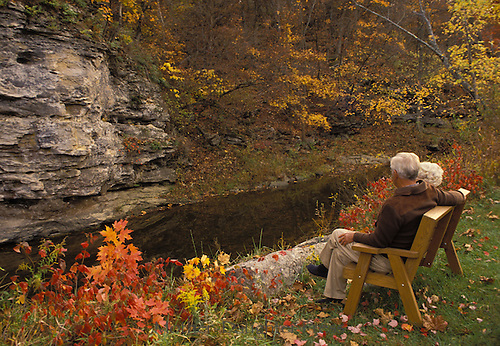 Mature couple, shares time on a fall afternoon in their backyard bench watching the creek and fall highlights, Midwest USA