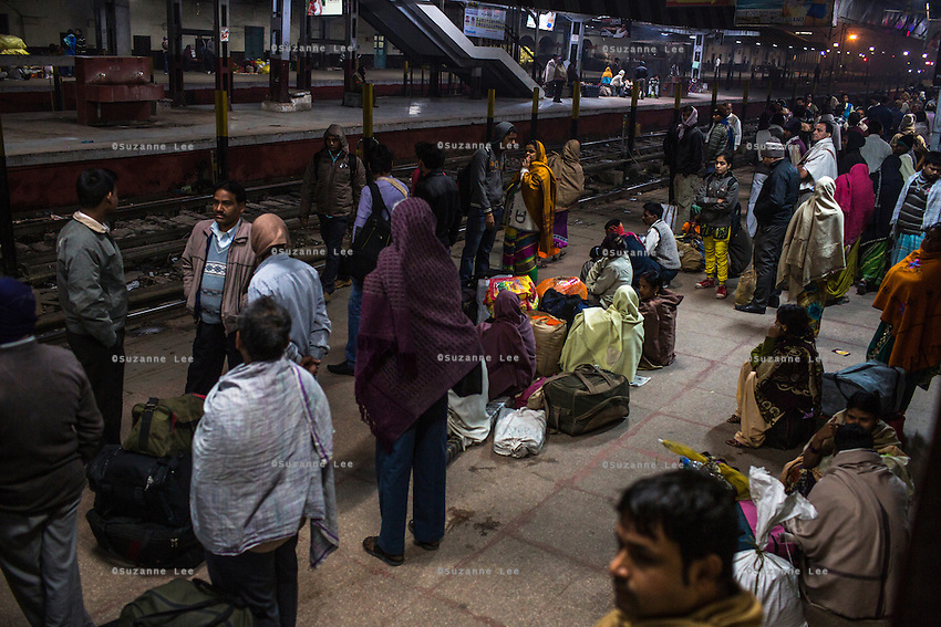 Passengers and family members wait for trains before the break of dawn at the Varanasi city railway station in Varanasi, Uttar Pradesh, India on 16 November 2013. Varanasi is a major religious tourist city and in the sex trade, a major source, transit and destination point for trafficked girls and women.