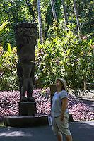 "A woman looks up near a carved wooden tiki of the Hawaiian god ""KU"" at Hawai'i Tropical Botanical Garden, Onomea, Big Island of Hawaiʻi."