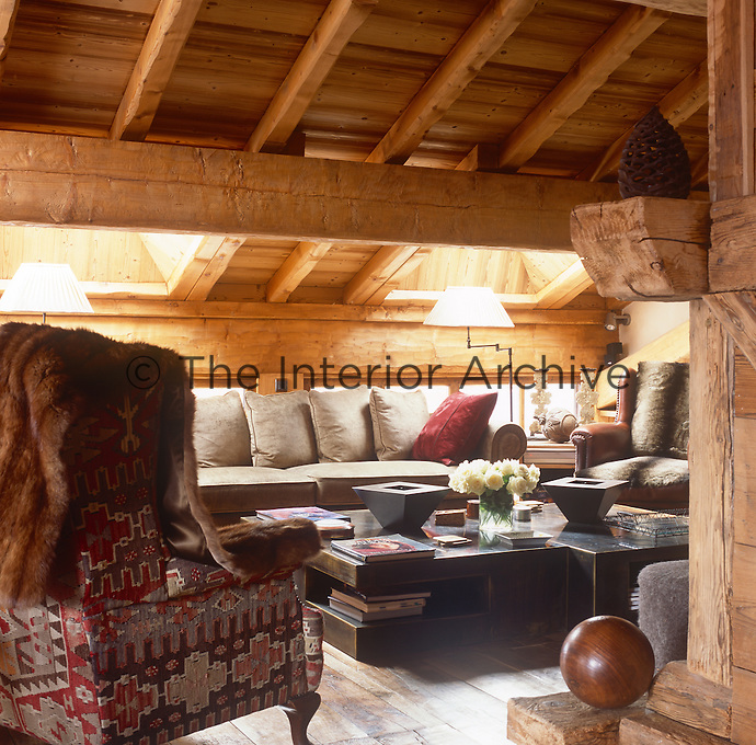 A view into a cosy living room in a rustic style room with a beamed ceiling and wood panelled walls. The room is furnished with two wingback chairs and a sofa placed around a coffee table.
