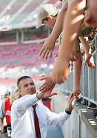 Ohio State Buckeyes head coach Urban Meyer high fives Boy Scouts as the team enters the field prior to the NCAA football game against Buffalo at Ohio Stadium on Aug. 31, 2013. (Adam Cairns / The Columbus Dispatch)