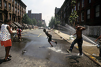 Youngsters cool off with water sprayed from a properly capped fire hydrant in a Harlem play street on July 6, 1994. (© Frances M. Roberts)