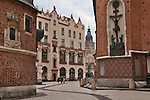 The narrow street between churches in Krakow, Poland with St. Mary's Church on the right and a view of the Town Hall Tower in the background
