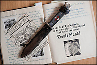 BNPS.co.uk (01202 558833)<br /> Pic: Mullocks/BNPS<br /> <br /> ***Please Use Full Byline***<br /> <br /> Hitler Youth dagger with swastika on the handle and potrait of Hitler with slogans in the diaries.<br /> <br /> Sinister archive illustrating the Nazi brainwashing of German youth comes to light...<br /> <br /> A chilling archive of an enthusiastic member of the Hitler Youth has emerged to highlight how the Nazi's brainwashed German children in the build up to WW2<br /> <br /> Helmut Nieboy kept detailed diaries during his time with the German equivalent of the Boy Scouts from 1933.<br /> <br /> Helmut also amassed a number of photographs of his time with the paramilitary group, showing the youngsters sitting around a campfire, marching and at rallies. <br /> <br /> The diaries also include incredibly detailed route marches as well as hand drawn portraits of the beloved Fuhrer with patriotic slogans.<br /> <br /> The archive, that also includes his Hitler Youth tent, knife and trumpet, are being sold by Mullock's Auctioneers of Shropshire.