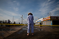 A Resident pauses at the boardwalk in Seaside park where a massive fire that engulfed dozens of businesses September 13, 2013 by Kena Betancur / VIEWpress
