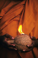 Sri Lanka. Buddhist nun holding a coconut and burning camphor at Kataragama. Coconuts are broken in front of the shrine when making a vow or giving thanks to the God's.